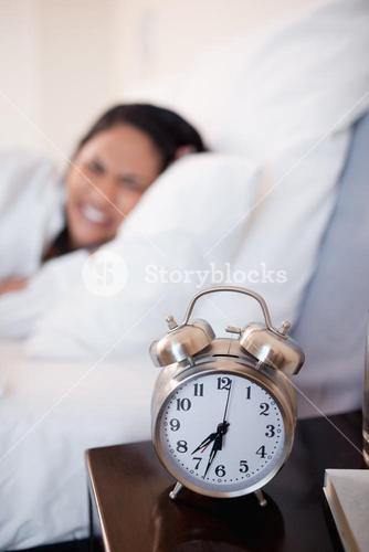 Alarm clock ringing next to woman in bed