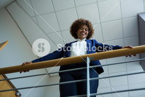 Businesswoman leaning over the railing of staircase