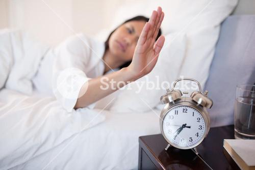 Alarm clock being turned off by woman