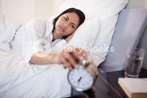 Woman annoyed by ringing alarm clock