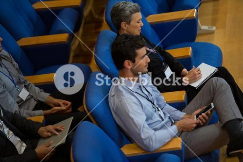 Business executive participating in a business meeting taking notes
