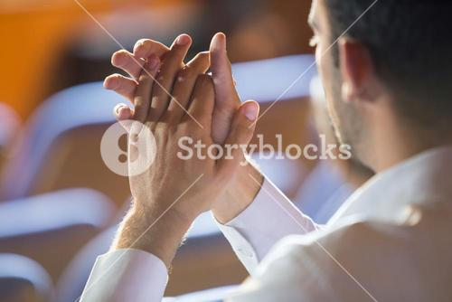 Business executive clapping while listening to speech