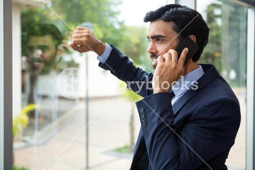 Businessman talking on mobile phone while looking through the window