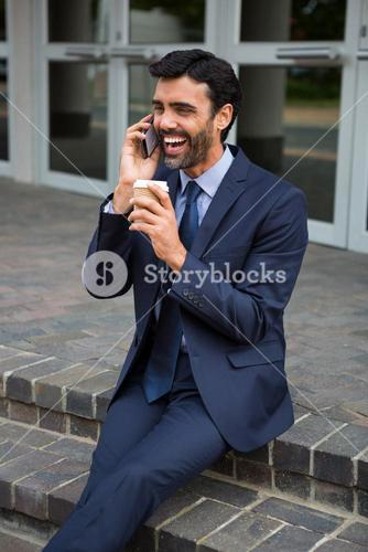 Businessman holding disposable coffee cup talking on mobile phone