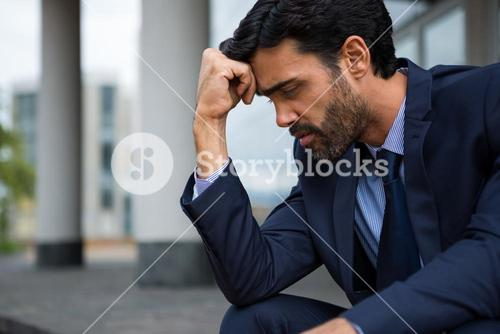 Depressed businessman sitting with hand on forehead