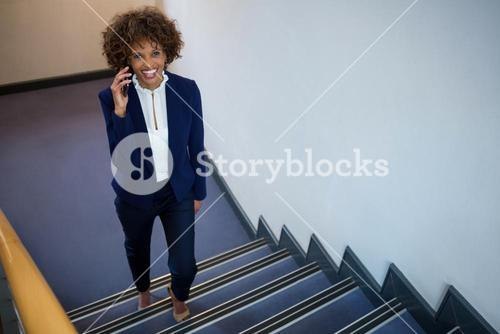 Businesswoman talking on mobile phone while walking upstairs