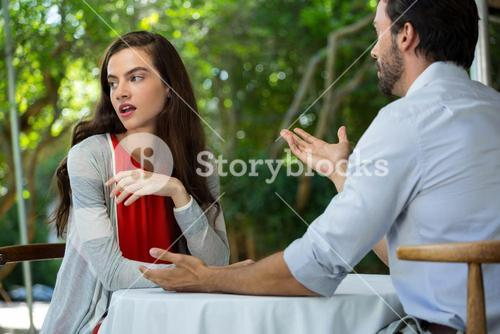 Couple having relationship difficulties at outdoor restaurant