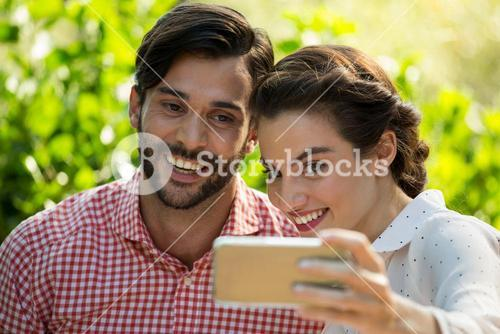 Cheerful couple taking slefie through smart phone at park