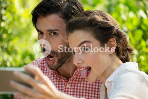 Playful couple taking slefie through mobile phone at park