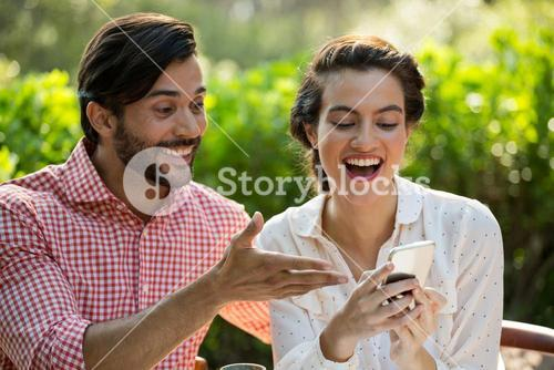 Happy couple using smart phone at park