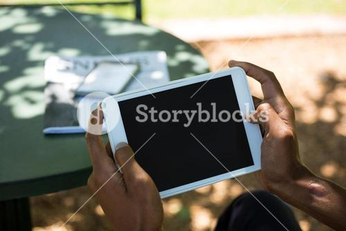 Businessman using digital tablet at outdoor restaurant