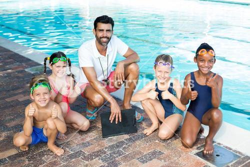 Swimming instructor with children at poolside