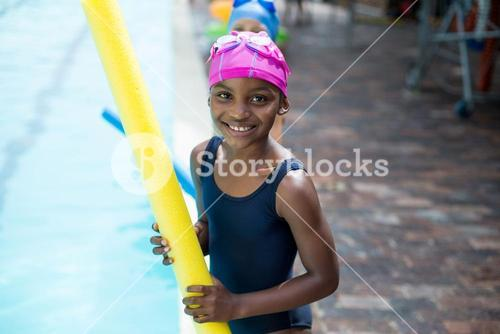 Girl holding pool noodle at poolside