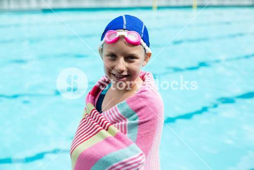 Girl wrapped in towel standing at poolside