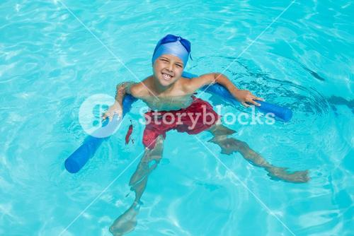 High angle view of cheerful boy swimming in pool