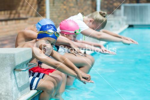 Swimming trainer teaching children at pool side