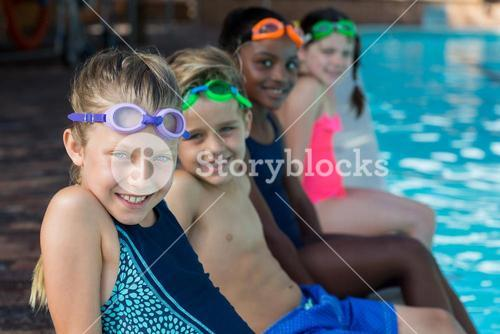 Row of friends sitting at pool side