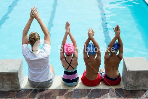 Swimming instructor teaching children at pool side