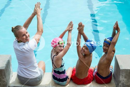 Swimming instructor with students at pool side