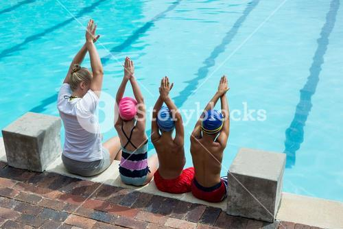 Female swimming instructor with students at pool side