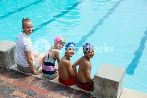 Cheerful swimming instructor and students at pool side