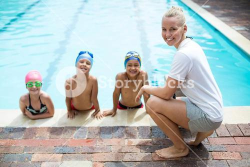 Female swimming trainer teaching students at pool side