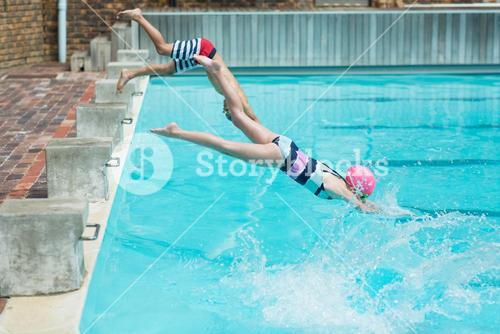 Children diving in water at poolside