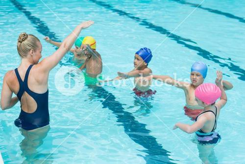 Trainer instructing students in swimming pool