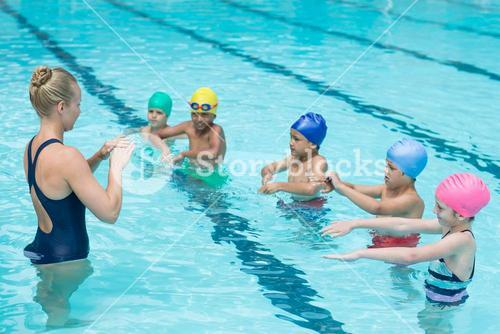 Swimming trainer instructing students
