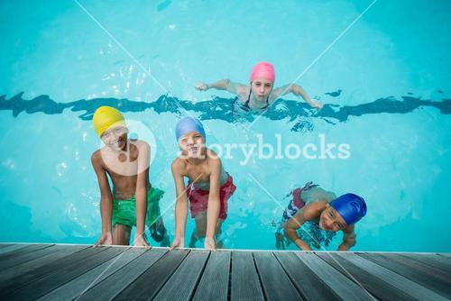 Happy girls and boys swimming in pool
