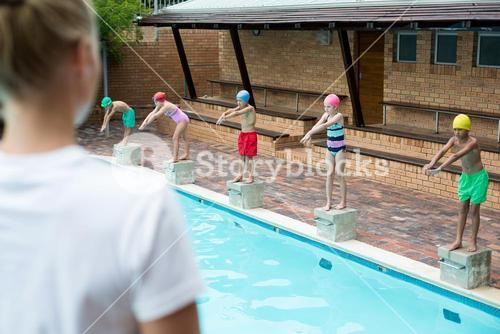 Female trainer looking at children at poolside