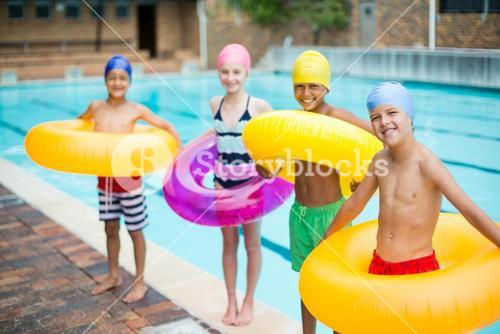 Friends carrying inflatable rings at poolside