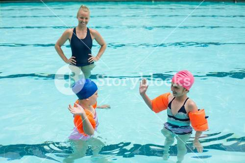 Female instructor and girls in swimming pool