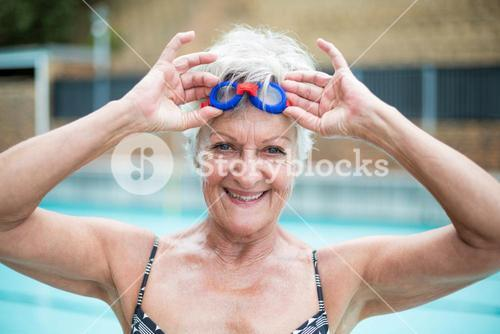 enior woman holding swimming goggles