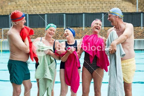 Happy senior swimmers wiping body with towels at poolside