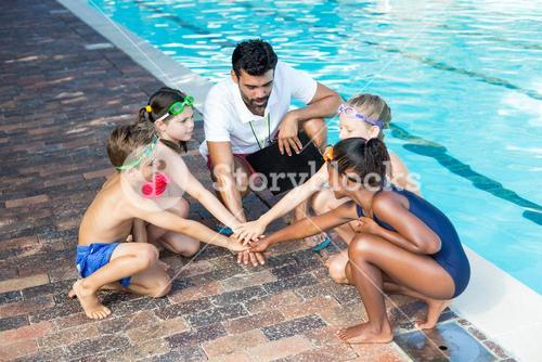 Instructor and children stacking hands at poolside