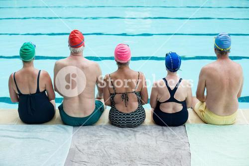 Senior swimmers sitting at poolside