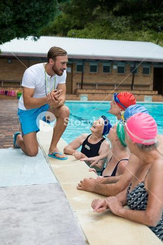 Swimming instructor assisting senior swimmers