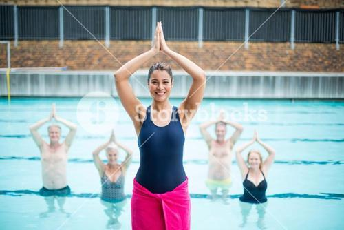 Female yoga instructor assisting senior swimmers at poolside