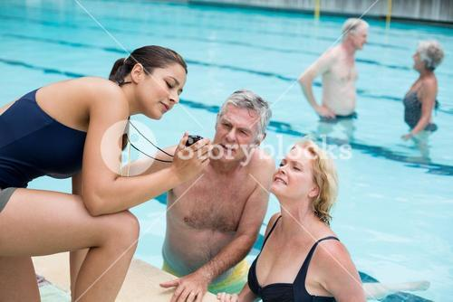 Female trainer showing time to senior swimmers at poolside