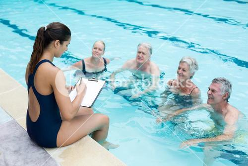 Female instructor writing while instructing senior swimmers at poolside