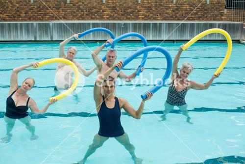 Trainer and senior swimmers exercising with pool noodle