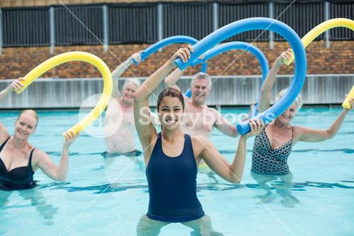 Cheerful trainer and senior swimmers exercising with pool noodle