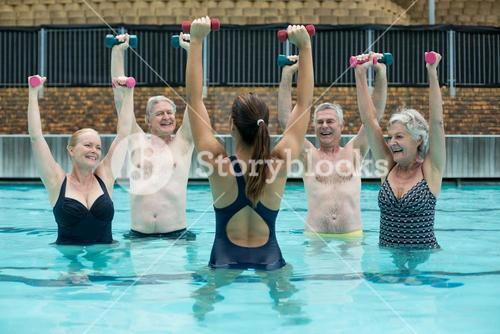 Swimmers enjoying weightlifting in swimming pool