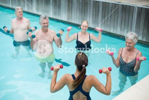 Trainer assisting senior swimmer in weightlifting