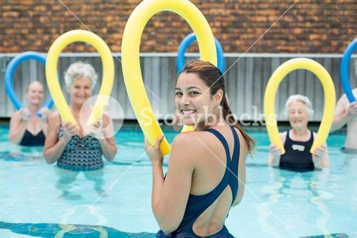 Trainer assisting senior swimmers with pool noodle