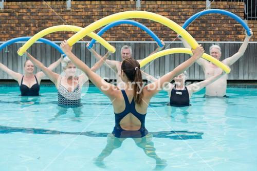 Instructor and senior swimmers exercising with pool noodle
