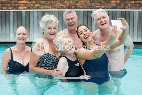 Female trainer taking selfie with senior swimmers in pool