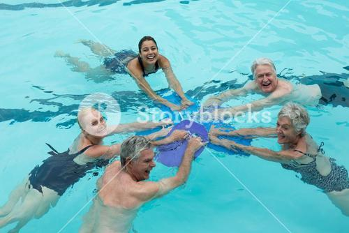 Cheerful trainers and senior swimmers in pool