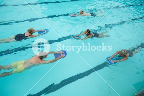 Trainer with senior swimmers swimming in pool